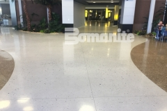 Concrete Arts expertly installed this Bomanite Modena Monolithic decorative concrete flooring in a soft gray color that was hand-seeded with mirrored glass, sea shells, and mother of pearl to create a shimmering effect that emulates shells and sea glass in the sun.