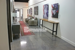 Featured here is Bomanite Patene Teres custom polished decorative concrete that was colored using Bomanite Black Orchid concrete dye and Polyurea joint filler in Gauntlet Grey to create a high gloss flooring surface that radiates warmth and elegance in this gallery space.