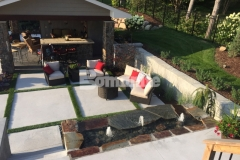 Concrete Arts installed Bomanite Revealed in this backyard resort to create the steps, landing, and beautiful courtyard area that is surrounded by planting pockets and inlays of grass to help with drainage, break up the expanse of concrete, and add warmth to the space.