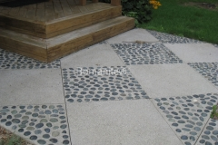 Concrete Arts skillfully installed this stunning salt and pepper Bomanite Revealed Exposed Aggregate concrete that was perfectly paired with these beautiful pebbles that were inset by hand to create a unique entrance into the client's home.