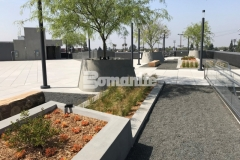 A gray Bomanite Exposed Aggregate Sandscape Texture finish was added to these lineal planters and circular tree planters to create textural detail that complements the unique design elements on this rooftop terrace at LAFC Stadium.
