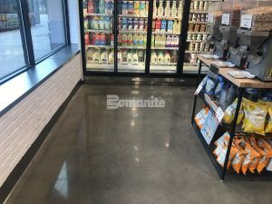 View of the Dairy Case and shelves in the Brothers Marketplace in Waltham, MA, featuring Bomanite Systems Custom Polished VitraFlor decorative concrete flooring installed by Premier Concrete Construction.