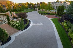 Long view of driveway towards street featuring Bomanite Exposed Aggregate Deep Washed Sandscape Texture System with a Buckskin Integral Color to Complement the Extravagant Courtyard, Basketball Brick Court and Stone Columns and Walls installed by Bomanite Toronto to withstand the Canadian Winters.