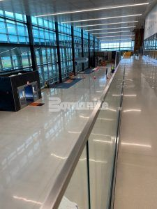Upper walkway looking down to the entrance at the newly renovated Brownsville South Padre Island International Airport in Brownsville, TX, featuring Bomanite Custom Polishing Modena SL System decorative concrete flooring installed by Texas Bomanite.