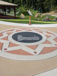 Splash pad, with a view towards a playground, using Bomanite Sandscape Texture Exposed Aggregate System with Bomanite Con-Color at the Community Park in Jefferson City, MO, installed by Bomanite Licensee Musselman & Hall Contractors, LLC.