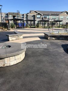 A view pool deck and cabana area at Icon Apartment Homes at Ferguson Farm in Bozeman, MT, installed by Bomanite licensee Architectural Concrete & Design using Bomanite Exposed Aggregate Systems with Bomanite Sandscape Texture and Bomanite Revealed.